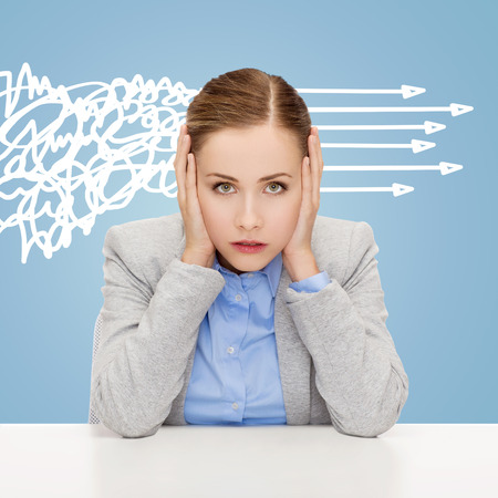 hands covering ears: business, education, emotional pressure and people concept - stressed businesswoman or student covering her ears with hands over blue background with messy and straight arrows