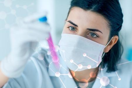 laboratorio clinico: la ciencia, la química, la biología, la medicina y la gente concepto - cerca de la mujer de ciencias tubo joven que sostiene con la toma de muestra y prueba o investigación en laboratorio clínico