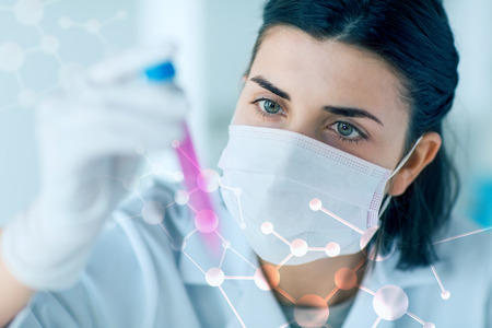 discovering: science, chemistry, biology, medicine and people concept - close up of young female scientist holding tube with sample making and test or research in clinical laboratory
