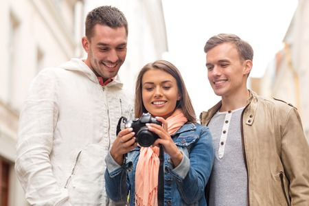 photocamera: travel, vacation, technology and friendship concept - group of smiling friends with digital photocamera