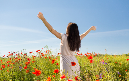 woman back view: happiness, nature, summer, vacation and people concept - young woman dancing on poppy field from back