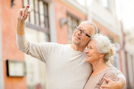 age, tourism, travel, technology and people concept - senior couple with camera taking selfie on street Stock Photo