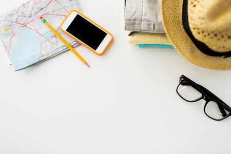 여행, 여름 휴가, 관광 및 개념을 객체 - 가까운 접힌 옷, 스마트 폰과 테이블에 관광지도까지