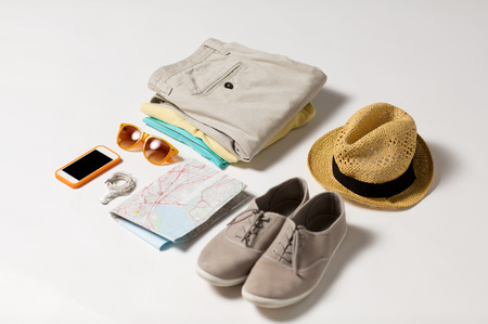 vacation map: summer vacation, tourism and objects concept - close up of clothes, smartphone, personal stuff and travel map