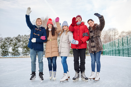 people, winter, friendship, sport and leisure concept - happy friends ice skating and waving hands on rink outdoors photo