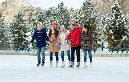patinando: gente, invierno, la amistad, el deporte y el concepto de ocio - amigos felices de patinaje sobre hielo en la pista de patinaje al aire libre