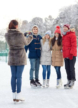people, friendship, technology and leisure concept - happy friends taking picture with smartphone on ice skating rink outdoors photo