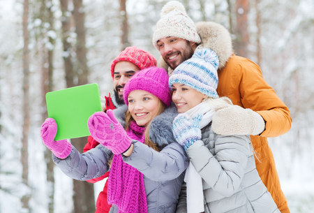 technology, season, friendship and people concept - group of smiling men and women taking selfie tablet pc computer in winter forest photo