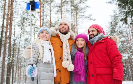 technology, season, friendship and people concept - group of smiling men and women taking selfie with smartphone and monopod in winter forest photo