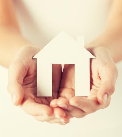 costruction: closeup pisture of woman hands holding paper house