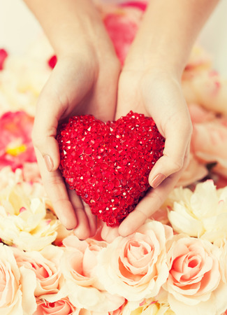 propose: close up of womans hands holding heart