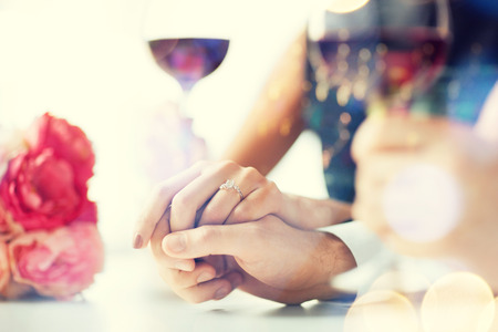 parejas romanticas: amor, la familia, el concepto de aniversario - pareja comprometida con copas de vino en el restaurante Foto de archivo