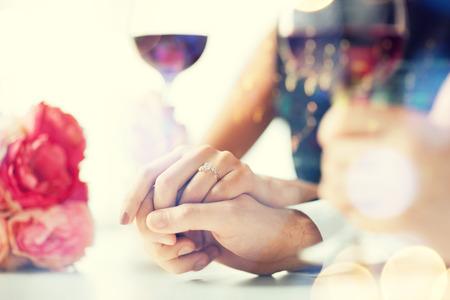 amor, la familia, el concepto de aniversario - pareja comprometida con copas de vino en el restaurante Foto de archivo