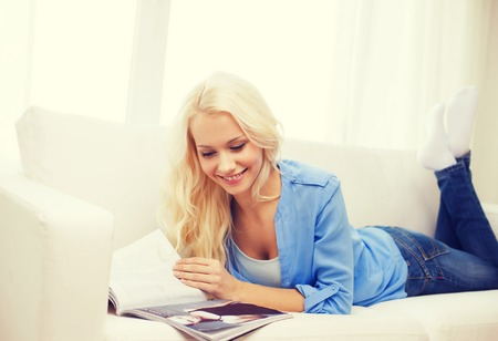 magazine reading: home and leasure concept - smiling woman lying on couch and reading magazine at home Stock Photo
