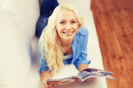 leasure: home and leasure concept - smiling woman lying on couch and reading magazine at home Stock Photo