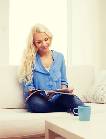 home and leasure concept - smiling woman with cup of coffee or tea reading magazine at home Stock Photo