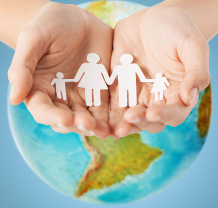 human palm: people, population, charity and life concept - close up of human hands holding paper family over earth globe and blue background Stock Photo