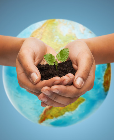 planeten: Menschen, Ökologie, Umwelt, Landwirtschaft und Ernährung Konzept - Nahaufnahme von der Hand Frau mit grünen spriessen über Erdekugel über blauem Hintergrund