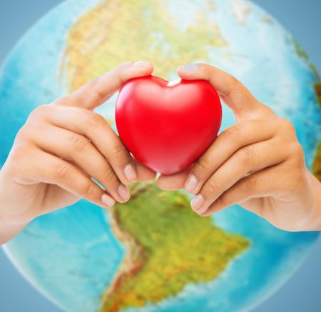 simbolo della pace: persone, l'amore, la salute, l'ambiente e la carità concetto - stretta di mani di donna che tiene cuore rosso sopra terra globo e sfondo blu