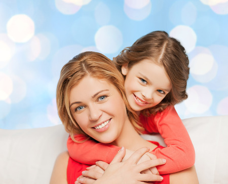 motherhood: people, happiness, love, family and motherhood concept - happy mother and daughter hugging over blue lights background