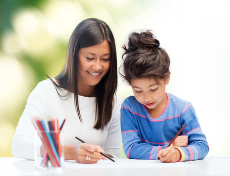 preteen asian: family, children, creativity and happy people concept - happy mother and daughter drawing with pencils over green background
