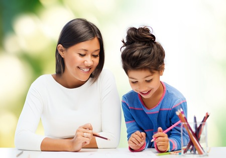 asian art: family, children, creativity and happy people concept - happy mother and daughter drawing with pencils over green background
