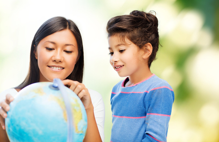 family, children, travel, geography and happy people concept - mother and daughter with globe over green background photo