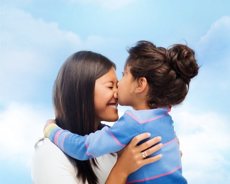 preteen asian: family, children and happy people concept - happy little girl hugging and kissing her mother over blue sky background Stock Photo