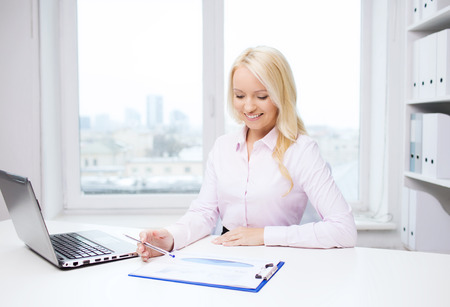 education, business and technology concept - smiling businesswoman or student with laptop computer and papers sitting in office photo