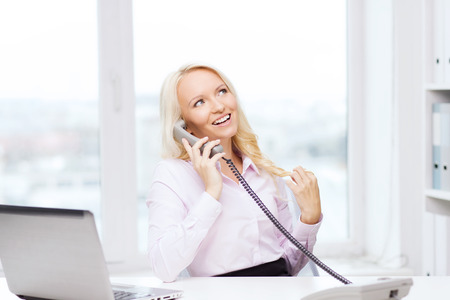 chatty: education, business, communication and technology concept - smiling businesswoman or student with laptop computer calling on phone in office Stock Photo