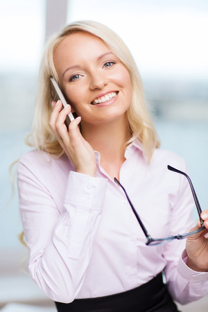education, business, technology, communication and people concept - smiling businesswoman or secretary wearing eyeglasses calling on smartphone  in office photo