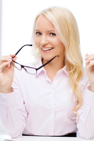 education, business,  vision and people concept - smiling businesswoman, student or secretary wearing eyeglasses in office photo