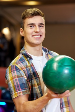 happy young man: people, leisure, sport and entertainment concept - happy young man holding ball in bowling club
