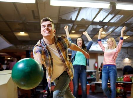 人、レジャー、スポーツ、エンターテイメントのコンセプト - ボウリング クラブでボールを投げて幸せな若い男