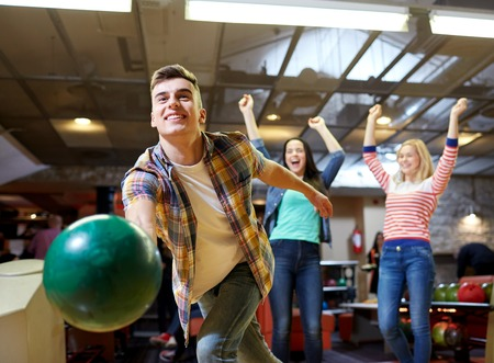 rooting: people, leisure, sport and entertainment concept - happy young man throwing ball in bowling club