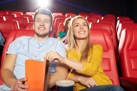 watching movie: cinema, entertainment and people concept - happy friends watching movie in theater