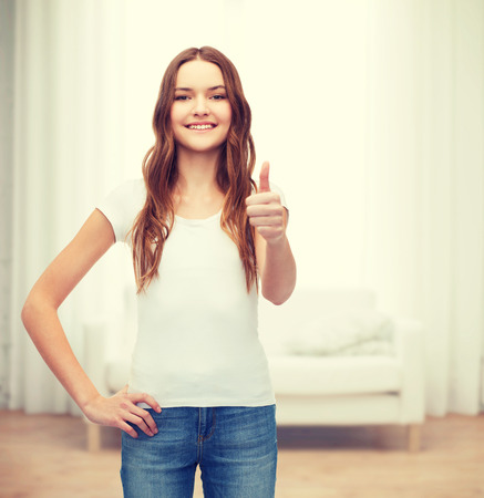 beautiful teen girl: t-shirt design concept - smiling teenager in blank white t-shirt showing thumbs up