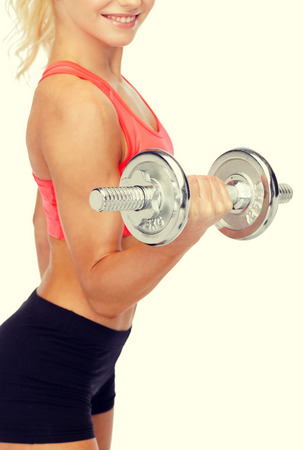 musculine: fitness, healthcare and exercise concept - close up of young sporty woman with heavy steel dumbbell