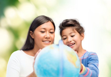 asian teacher: family, children, education, geography and people concept - happy mother and daughter with globe over green background