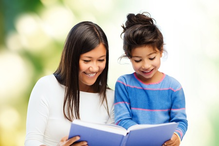 asian child: family, children, education and happy people concept - happy mother and little daughter reading book over green background