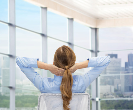 view of an elegant office: business, education, people and office concept - businesswoman or teacher sitting on chair from back over office window background