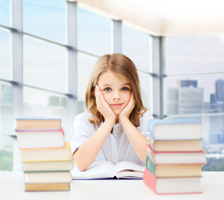 primary education: education, people, children and school concept - little student girl sitting at table with books and writing in notebook over classroom background Stock Photo