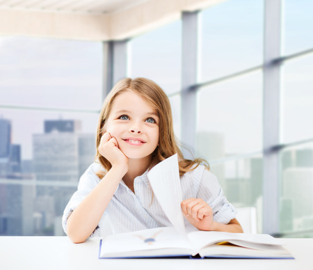 primary school: education, people, children and school concept - little student girl sitting at table with books and writing in notebook over classroom background Stock Photo