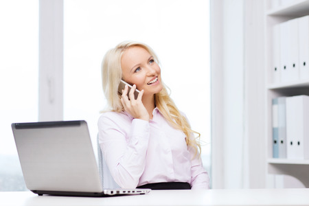 chatty: education, business, communication and technology concept - smiling businesswoman or student with laptop computer calling on smartphone in office