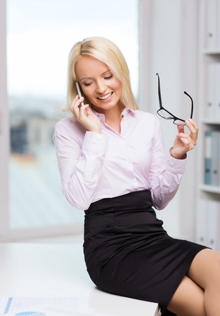 sexy teacher: education, business, technology, communication and people concept - smiling businesswoman or secretary wearing eyeglasses calling on smartphone  in office