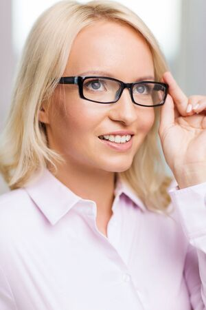 to the secretary: education, business,  vision and people concept - smiling businesswoman, student or secretary wearing eyeglasses in office