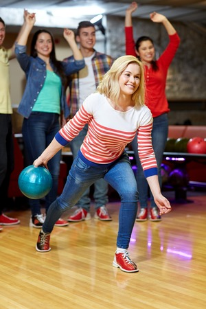 people, leisure, sport and entertainment concept - happy young woman throwing ball in bowling club photo