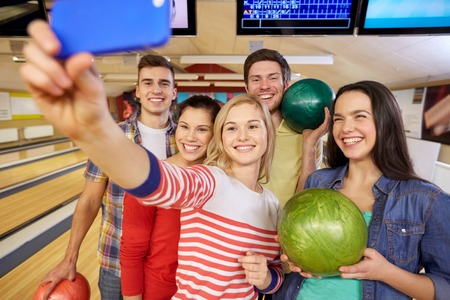 people, leisure, sport, friendship and entertainment concept - happy friends taking selfie with smartphone in bowling club Stock Photo