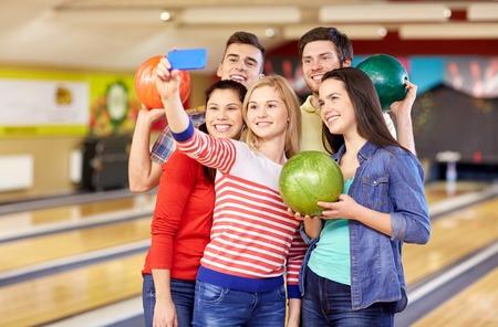 bolos: la gente, el ocio, el deporte, la amistad y el concepto de entretenimiento - amigos felices que toman Autofoto con el teléfono inteligente en el club de bolos Foto de archivo