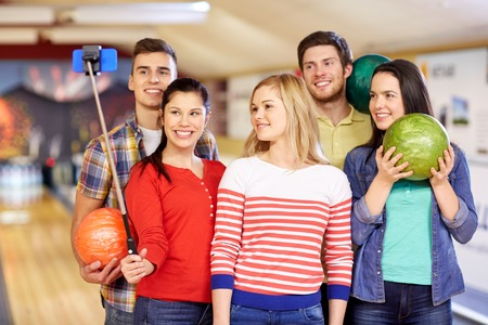 people, leisure, sport, friendship and entertainment concept - happy friends taking selfie with smartphone on monopod in bowling club